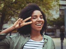 Glimlachende jonge vrouw die vredesteken tonen stock foto