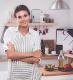 Glimlachende jonge vrouw die zich in de keuken bevinden Royalty-vrije Stock Foto