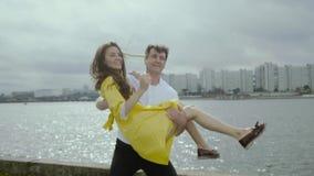 Glimlachende jonge vrouw en man dans grappige dans op een dok in een regenachtig weer stock videobeelden