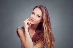 Glimlachende jonge vrouw, hand die op wang u bekijken die veronderstellen stock fotografie