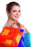 Glimlachende jonge vrouw het glimlachen dragende het winkelen zakken Stock Foto's