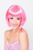 Glimlachende jonge vrouw in het roze pruik stellen op witte achtergrond Royalty-vrije Stock Foto's