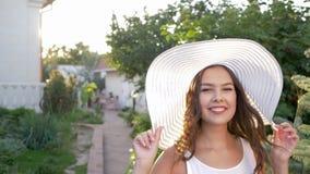 Glimlachende jonge vrouw in hoed met brede die rand naar zich en looppas vooruit wordt aangetrokken stock video