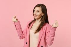 Glimlachende jonge vrouw in jasje die vingers wrijven, die contant geldgebaar tonen, die om geld vragen op pastelkleur roze muur  stock fotografie