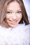 Glimlachende jonge vrouw met blauwe ogen en witte boa Stock Afbeeldingen