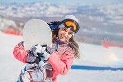 Glimlachende jonge vrouw met het snowboarding op de berg in de winter stock foto's