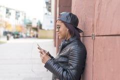 Glimlachende jonge vrouw met hoofdtelefoons en slimme telefoon het luisteren muziek in de straat stock afbeelding