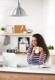 Glimlachende jonge vrouw met koffie binnen kop en laptop Royalty-vrije Stock Afbeeldingen