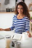 Glimlachende jonge vrouw met koffie binnen kop en laptop Stock Afbeeldingen