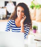 Glimlachende jonge vrouw met koffiekop en laptop in de keuken thuis Stock Foto