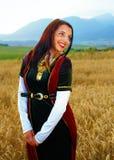 Glimlachende Jonge vrouw met middeleeuwse kleding status Stock Afbeelding