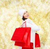 Glimlachende jonge vrouw met rode het winkelen zakken Royalty-vrije Stock Afbeeldingen