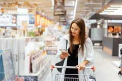 Glimlachende jonge vrouw met smartphone in supermarkt stock foto
