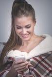 Glimlachende jonge vrouw met smartphone thuis Stock Afbeeldingen
