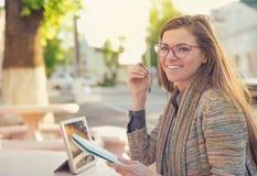 Glimlachende jonge vrouw met studies in openlucht royalty-vrije stock foto