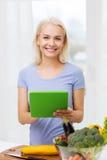 Glimlachende jonge vrouw met tabletpc die thuis koken Stock Foto's