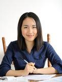 Glimlachende jonge vrouw na de voltooiing van IRS belastingsvormen stock afbeeldingen