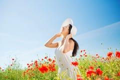 Glimlachende jonge vrouw in strohoed op papavergebied Royalty-vrije Stock Foto