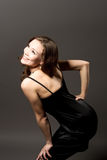 Glimlachende jonge vrouw in zwarte kleding stock afbeelding