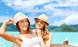 Glimlachende jonge vrouwen in hoeden op het strand van borabora stock foto