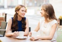 Glimlachende jonge vrouwen met koffiekoppen bij koffie Royalty-vrije Stock Foto