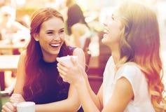 Glimlachende jonge vrouwen met koffiekoppen bij koffie stock afbeeldingen