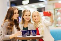 Glimlachende jonge vrouwen met koppen en smartphone Stock Foto's