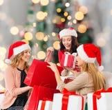 Glimlachende jonge vrouwen in santahoeden met giften Royalty-vrije Stock Afbeeldingen