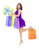 Glimlachende jonge vrouwenholding het winkelen zak en een giftdoos Stock Afbeeldingen