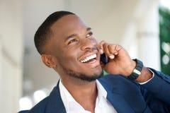 Glimlachende jonge zakenman die door mobiele telefoon roepen Royalty-vrije Stock Foto
