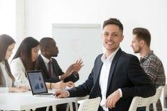 Glimlachende jonge zakenman die in kostuum camera op vergadering bekijken stock foto's