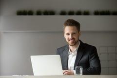 Glimlachende jonge zakenman die in kostuum met laptop camera bekijken royalty-vrije stock foto's