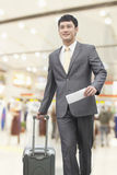 Glimlachende jonge zakenman die met koffer en het houden van vluchtkaartje bij de luchthaven lopen Royalty-vrije Stock Foto's