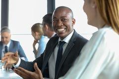 Glimlachende jonge zakenman die met vrouwelijke collega in raadsruimte bespreken Stock Foto's