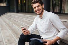 Glimlachende jonge zakenman die mobiele telefoon in openlucht met behulp van royalty-vrije stock afbeelding