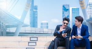 Glimlachende jonge zakenman die van een positief gesprek genieten die met een rijpe partner in een moderne ruimte in stad spreken stock foto