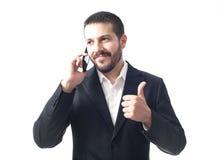 Glimlachende jonge zakenman op de telefoon met omhoog duimen Royalty-vrije Stock Foto