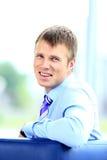 Glimlachende jonge zakenman op kantoor. Stock Afbeeldingen