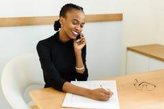 Glimlachende jonge zwarte bedrijfsvrouw op telefoon die nota's in bureau nemen Stock Foto