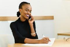 Glimlachende jonge zwarte bedrijfsvrouw op telefoon die nota's in bureau nemen Stock Fotografie