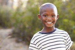 Glimlachende jonge zwarte jongen die aan camera in openlucht kijken stock foto's