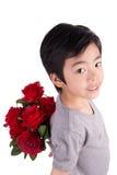 Glimlachende jongen die een boeket van rode rozen achter zich verbergen, isolat Stock Foto's
