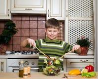 Glimlachende jongen die een plantaardige salade in de keuken mengen. Stock Foto's