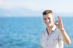 Glimlachende jongen die o.k. teken op overzeese achtergrond tonen Stock Fotografie