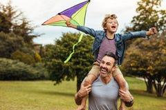 Glimlachende jongen die op vadersschouders met vlieger spelen royalty-vrije stock afbeelding