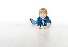 Glimlachende jongen die op witte vloer liggen Royalty-vrije Stock Foto