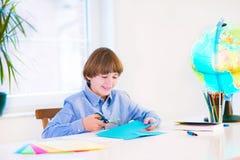 Glimlachende jongen die thuiswerk doet Stock Afbeeldingen
