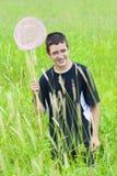 Glimlachende jongen die vlinders in de weide vangen Stock Fotografie