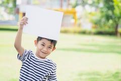 Glimlachende jongen die zich met lege horizontale spatie in handen bevinden Leuk weinig jongen met wit blad van document stock fotografie