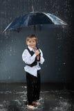 Glimlachende jongen die zich onder paraplu in regen bevindt Stock Foto's